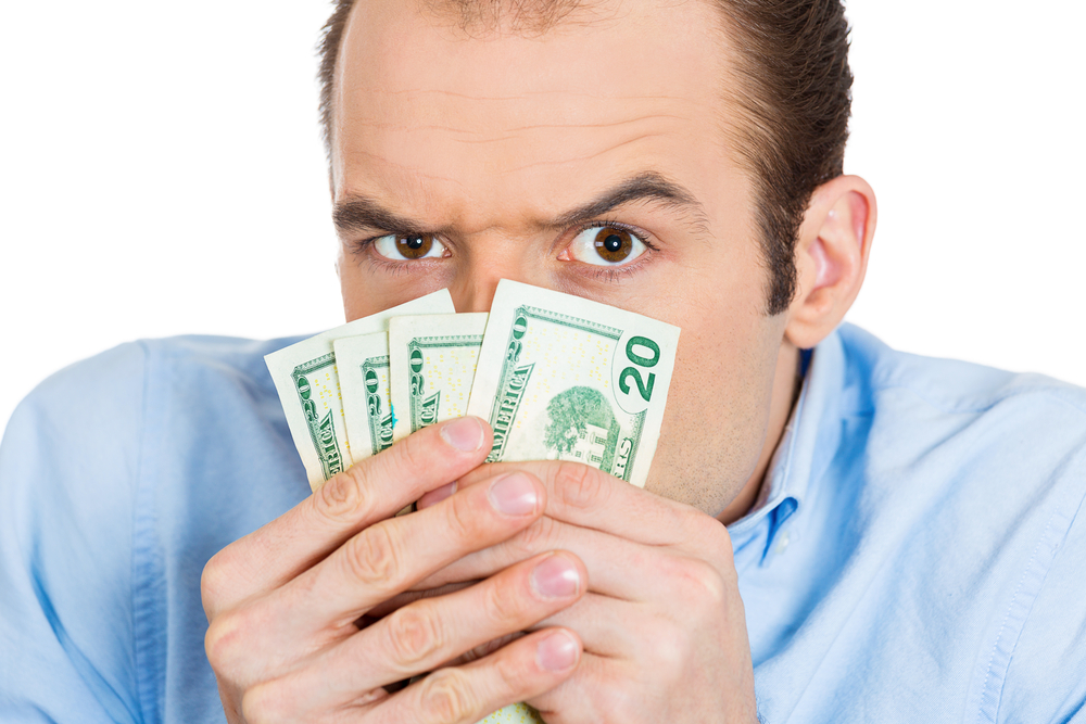 Closeup portrait of greedy banker executive CEO boss, corporate employee funny looking man, shaking holding dollar banknotes scared to loose money, suspicious isolated on white background. Expressions